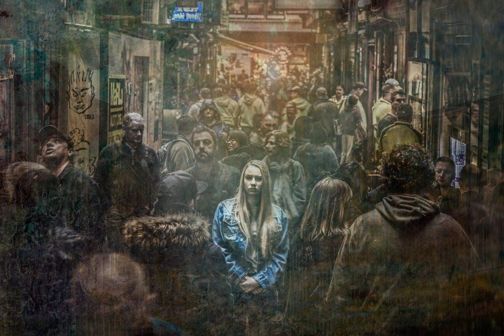 Vrouw staat alleen en gestressed in drukke menigte